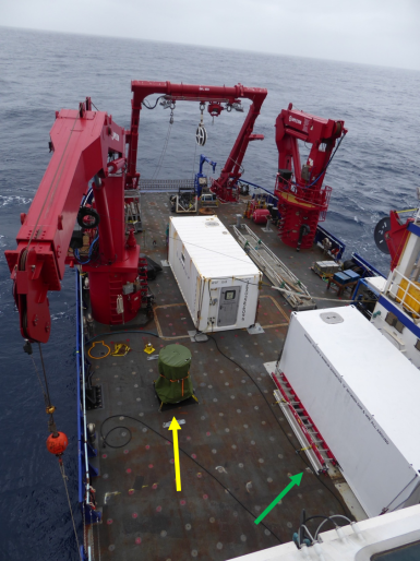 """Here's the deck of our ship, the R/V Sikuliaq. The green arrow is pointing to the """"Trace Metal Clean Van"""" –it's not really a van, but there are two rooms inside where we keep our bottles and do our filtering. The yellow arrow is pointing to our trace metal CTD. We have to keep it covered when we're not using it so it doesn't get dirty!"""